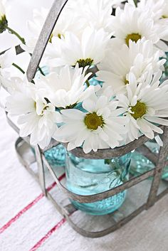 Love the white daisies in blue canning jars.