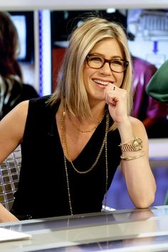Jennifer Aniston short hair, glasses, gold watch.