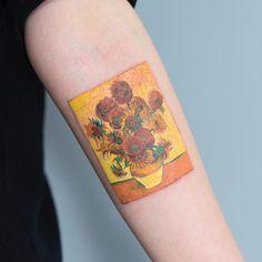 Tatuagem criada por Zihee Tattoo da Coréia do Sul. Tatuagem em forma de quadro no braço com flores amarelas.
