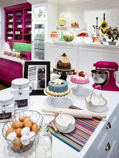This fun and cheery kitchen features white countertops and cabinets paired with colorful accents, like a fuchsia built-in hutch and bright green tile backsplash. Alice in Wonderland decorations add a whimsical touch, while multiple cake stands feature gorgeous cakes and other desserts.