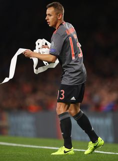 Rafinha of Bayern Muenchen removes a streamer from the pitch during the UEFA Champions League Round of 16 second leg match between Arsenal FC and FC Bayern Muenchen at Emirates Stadium on March 7, 2017 in London, United Kingdom.