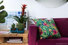 Mesa lateral feita com pallets empilhados, sofá na cor beringela e almofada com estampa tropical.