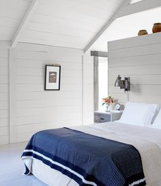 white wood walls, partial wall headboard dividing bathroom