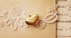 Dettaglio a forma di cuore dorato per delle partecipazioni romantiche: cerca il tuo fornitore sul nostro portale >> http://www.lemienozze.it/operatori-matrimonio/partecipazioni_e_tableau/