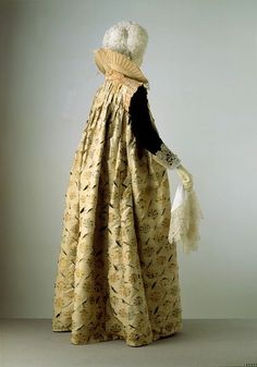 This loose gown made of Italian brocaded silk would have been worn by a woman in the early 17th century as part of a formal day ensemble. A bodice and petticoat of equally luxurious, although not necessarily matching materials would have been worn underneath. The silk has been slashed between the brocaded motifs. This was a popular decorative technique during the 16th and early 17th centuries. At the centre back of the gown's small upright collar are two holes to fasten a support for an…