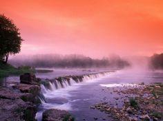 Sunrise in the morning mist over the waterfall on the Venta River near Kuldiga, Latvia by Janis Miglavs