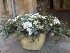 Cesto pequeño natural con combinación de flores blancas, hojas y ramas verdes.
