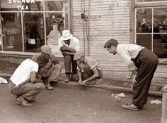 picture of men playing dice. The picture shows miners outside the company store in Osage, West Virginia.