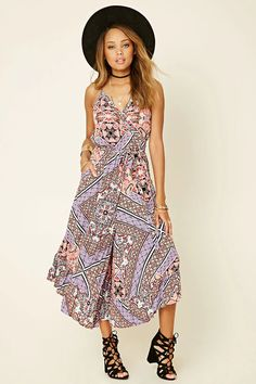 A woven abstract print maxi dress with adjustable cami straps, a mock wrap self-tie waist, a surplice front, a scoop back, slanted side pockets, and an elasticized waist. This is an independent brand and not a Forever 21 branded item.