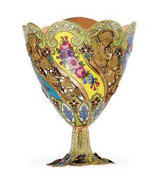 A SWISS TWO-COLOR GOLD AND ENAMEL ZARF <br />GENEVA, CIRCA 1830 <br />With scalloped border, the sides with swirling flutes of pink, blue and yellow enamel, painted with flowerheads in between open-work relief panels of grape vine, <i>apparently unmarked</i><br />2 3/8 in. (6 cm.) high <br />