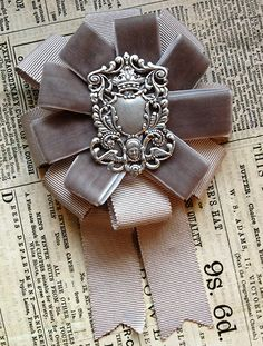 this+rosette+features+a+vintage+silvertone+filigree,+surrounded+by+tiers+of+grey+velvet+and+petersham+grosgrain+ribbons. this+rosette+measures+approximately+4+inches+wide+and+6+inches+tall. all+mossbadger+rosettes+have+a+combination+back+so+they+can+be+worn+as+a+brooch+or+hairclip.