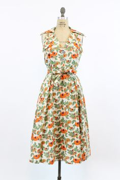 Stunning 1940s floral sundress! Halter neckline with a low v-cut back. Bodice is adorned with 2 large abalone diamond cut buttons. Nipped in