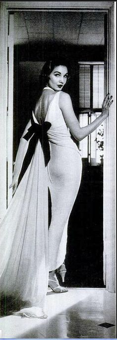 1956 Sherry Nelms in evening dress of white silk with deeply cut back by Luis Estevez. It has black velvet bow to anchor the floating chiffon train