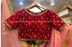 Stunning red color designer blouse with boat neck and floral design hand embroidery silver thread work allover.