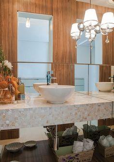 Ambiente de dimensões reduzidas, o lavabo é puro requinte, com bancada com pastilhas de madrepérola, arandela com pingente de cristal e plaf...