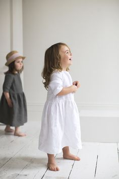 Linen Girl's Dress | White. Our soft, pretty linen dresses will delight little girls who dream of whimsical fairytales. The comfortable crew neck and elbow length sleeves make it exceptionally easy to wear and move around in, and a simple mother-of-pearl button fastening on the back and a gently gathered waist create a beautiful, timeless shape.  #thelinenworks #linen #childrenclothing #kidschothing #girlsdresses #linendress #stylishkids