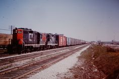 westbound CN Montreal-Toronto time freight-note intermodal in the train-unusually hauled by GP9's, #4513 and #4514, as it rolls by Scarboro GO station on May 7, 1977.