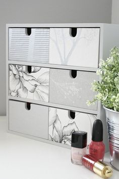 Painted paper images cut to glue to the drawer fronts, which have all been painted light grey.