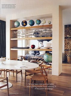 Domino - May 2008; oval swan table with hans wegner wishbone chairs; open shelf divider, globes