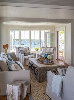 Stylish Coastal Living Room with thick woven rug and large wooden coffee table. Cozy Coastal!