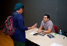 """Novelist and Short Story Writer Manuel Muñoz speaks with a student as he signs a copy of his Hitchcock-inspired debut novel, """"What You See in the Dark"""" at Dewberry Hall in the Johnson Center, Fairfax Campus during the 2011 Fall for the Book festival. Photo by Alexis Glenn"""