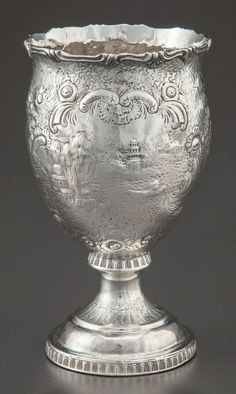 A Gale & Hayden coin silver goblet from around 1850. Pyriform goblet with shaped rim, scroll decoration. The sides have landscapes scenes and a plain shield.