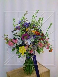 See this image on Clements Farm: Wildflower wedding bouquet for an early July wedding featuring larkspur, cosmos and geum