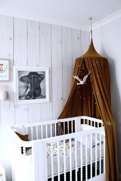 Gold numero 74 canopy. Incy Interiors vintage inspired Georgia cot. Wood look wall paper. Gender Neutral boy or girl nursery / baby room. Whimsical meets bohemian.