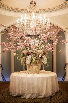Escort cards were displayed on a round table adorned with ivory filigree fabric. A lush arrangement of orchids, peonies, hydrangeas, and roses topped the displ… Hotel Flower Arrangements, Peony Arrangement, Wedding Arrangements, Wedding Centerpieces, Wedding Reception Flowers, Reception Decorations, Wedding Table, Floral Wedding, Wedding Ceremony