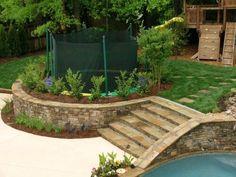 Anstatt das Trampolin im Boden zu begraben, wurde der Boden rund um das Trampolin aufgebaut. Dies bietet die gleiche Sicherheitsvorteile als es vergraben sondern auch können Sie mit Landschafts- und Gardenwork spielen.