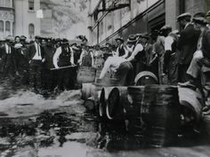 Los Angeles County Sheriff's Deputies busting barrels of alcohol during prohibition.