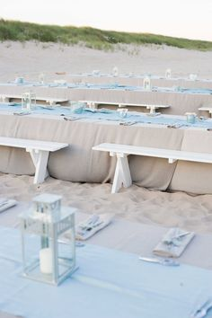 White picnic benches at wedding reception rehearsal dinner on sand beach