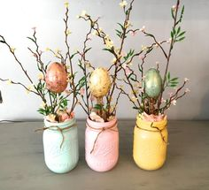 """EASTER HOME DECOR IDEA. This mason jar centerpiece is perfect for your home or event! Great for weddings, parties and home decor. The wooden planter box measures 13.5 x 5 x3.5"""" and fits 3 pint size mason jars which have been painted ocean breeze, candy pink and summer squash. Each jar will have spring florals and one easter egg. #affiliate"""