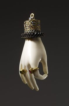 Pendant amulet in the form of an ivory hand with gold enameled cuff; gold rings on two of the fingers, one set with a garnet, the other with an emerald, c. 1600. Spain or Italy.