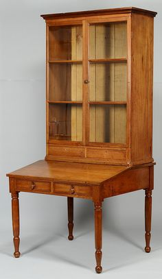 """Middle Tennessee Sheraton walnut desk and bookcase or """"plantation desk,"""" Two part construction. Upper section with ogee cornice over two triple-pane glazed doors, three interior shelves, over two drawers with diamond inlaid escutcheons. Shelves in upper section align with transoms on doors. Base section has slanted top surface over two dovetailed drawers with raised oval escutcheons, and tall turned legs. 85 3/4"""" H x 39 3/4"""" W x 35"""" D. Circa 1835."""