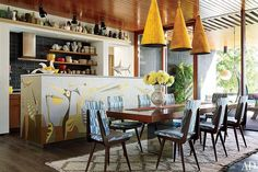Adler chairs covered in a Lee Jofa fabric surround a vintage Milo Baughman table from Vermillion 20th Century Furnishings; the kitchen island's mural is by John-Paul Philippé, and the range hood is by Electrolux.