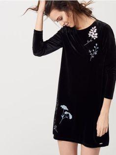 Mohito - Aksamitna sukienka  Sukienka o prostym fasonie, który ładnie podkreśli zgrabne nogi. Wykonana z czarnej tkaniny o aksamitnym wykończeniu. Posiada ozdobne haftowania z kwiatowym wzorem. Długie rękawy.