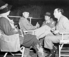 edium BTS shot of Ray Bolger as the Scarecrow, director Victor Fleming, choreographer Bobby Connelly and producer Mervyn LeRoy, all seated in directors chairs.