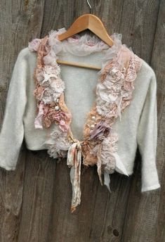 Whimsy little soft cardi (angora blend) in shades of cream, ivory, blush.. reworked and adorned with tattered old laces and torn silks, abstract sculpted pale blush chiffon blooms, tulle, cotton; textured, hand stitched, accentuated with ivory and cream pearls. Fastens with hand dyed