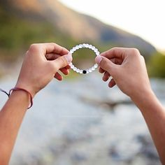 Lokai Bracelet - IN LOVE with this concept! The bracelet is infused with elements sourced from the highest and lowest points on Earth. The white ball, carrying water from Mt. Everest, and the black ball, holding mud from the Dead Sea, exist on opposite ends. A string of clear beads link the two, signifying that throughout life's circular journey, your path is your own.