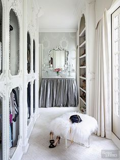 Doesn't this look like the French version of Carrie Bradshaw's closet? Whereas Carrie's Fifth Avenue wardrobe was sleek and clean, this Parisian-style apartment is outrageously chic. We can't get over the egg-and-dart molding and cut-glass knobs on the doors, not to mention that gathered silver vanity skirt. Cap it all off with a Lucite ottoman and curly sheepskin topper, and you've got the most glam off-screen closet around. Consider us totalement amoureux./