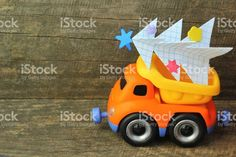 Toy truck carrying hand made paper christmas tree against rough wooden background. Side view. Christmas tree recycle or disposal, utility service royalty-free stock photo