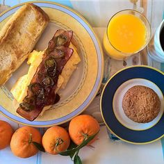 Saturday breakfast spread: A hearty spicy sandwich with soft bread, cheese, an omelette with more than a handful of shredded mature cheddar, HP sauce, glazed bacon and glazed pickled jalapeños, one of her muffins and a bunch of tangerines. #thenewbreakfasteverydayproject #livingmylifemyway