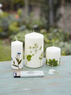 Fill the jar with boiling water. Decorating the candles one by one, dip a candle into the water, holding it by the wick, and keep it submerged for about 1 1/2 minutes. Using tweezers, quickly press the herbs onto the softened wax...