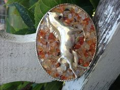 Vintage sterling horse pin set into on oval buckle surrounded by amber colored stone chips