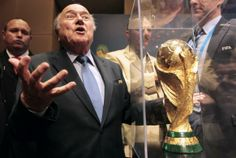 FIFA President Sepp Blatter gestures next to the World Cup trophy after a media conference in Sao Paulo, Brazil, June 5, 2014. REUTERS/Paulo Whitaker