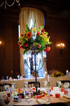 Iron candelabra with orange Gerber daisies, red and coral roses, and green snapdragons | Lasting Images Photography | villasiena.cc