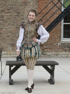 A lady in nobleman's clothing: doublet, trunk hose, hose, and striking black leather shoes.