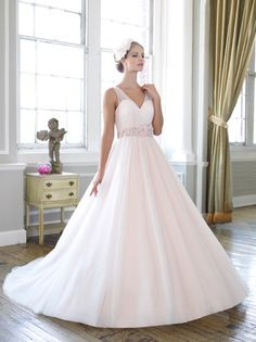 A flowing ball gown that features an intricate micro-beaded and floral sash. Soft tulle is pleated and draped over the sweetheart bodice creating illusion sleeves.