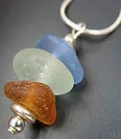 """The trio of 1"""" Pacific Ocean sea glass forms a pendant that has been accented with 4 base metal beads. It hangs on an 18"""" sterling silver snake chain. Your necklace will arrive in a cotton lined gift box and on a card that tells the short story of sea glass and the name of the ocean your pieces where they were beachcombed."""